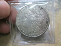 1892-CC MORGAN SILVER DOLLAR IN ABOUT UNCIRCULATED CONDITION