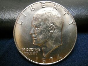 1974 UNCIRCULATED IKE DOLLAR . SPOTS ON REVERSE. COMBINE SHIPPING.