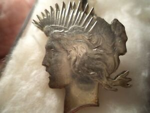 CARVED PEACE SILVER DOLLAR INTO A TIE PIN.